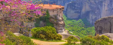 Orthodox Varlaam Monastery in Meteora, Greece on high mountain rock and pink cherry tree flower blossom