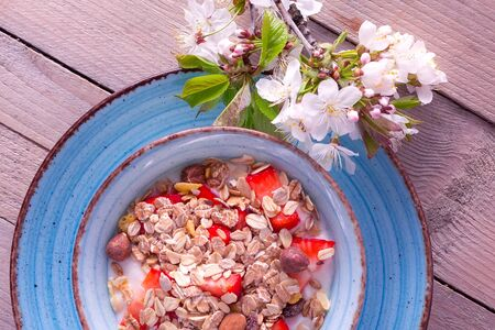 Healthy breakfast, muesli with fresh strawberry and yogurt bowl and white flowers still-life on rustic wooden background