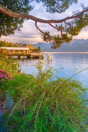 Panoramic sunset view of Lake Geneva, Switzerland from Montreux promenade with colorful flowers, mountains behind