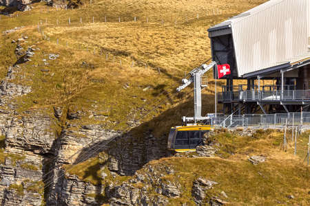 Wengen, Switzerland - October 10, 2019: Yellow cable car arriving from mountain village to viewpoint on cliff in Mannlichen