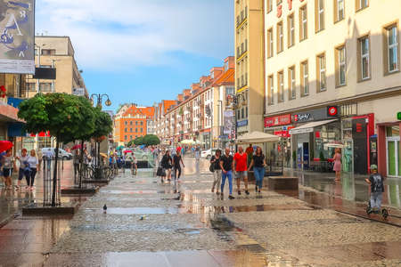 Wroclaw, Poland - June 21, 2019: Old town street view after rain, colorful houses and people