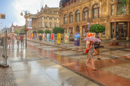 Wroclaw, Poland - June 21, 2019: Old town street view during the rain, colorful houses and people