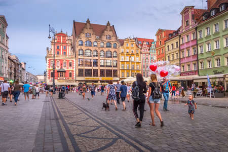 Wroclaw, Poland - June 21, 2019: Evening in Old Town Rynek Market Square, people and colorful houses