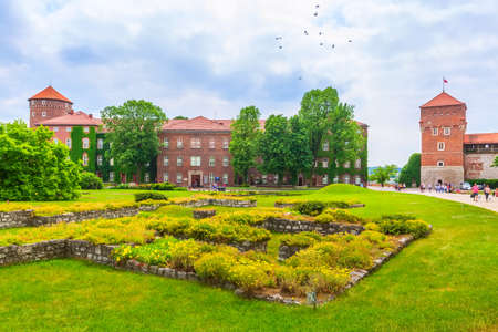 Krakow, Poland -June 18, 2019: Wawel Royal Castle colorful towers view against flower bed and green trees in the garden