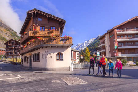 Zermatt, Switzerland - October 7, 2019: Town street view in famous swiss ski resort, colorful traditional houses, snow mountains panorama and people