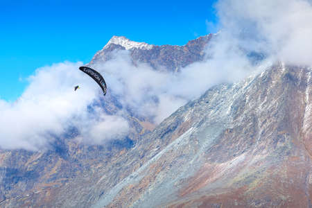 Zermatt, Switzerland - October 7, 2019: Paraglider over mountain snow peak, Swiss Alps