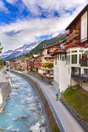 Zermatt, Switzerland - October 7, 2019: Alpine village panorama, Swiss Alps, traditional wooden houses, snow mountains and river Editorial