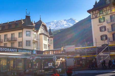 Zermatt, Switzerland - October 7, 2019: Town main street view in famous swiss ski resort, snow mountains and people