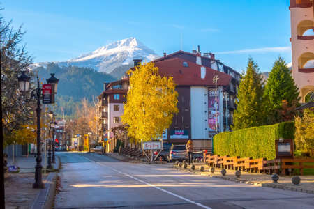 Bansko, Bulgaria - November 23, 2019: Autumn Pirin street view with houses and colorful trees