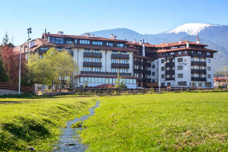 Bulgaria, Bansko - May 5, 2020: Sport hotel, green spring grass, melting snow water stream and snowy mountains
