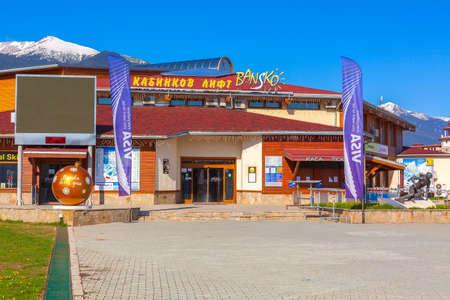 Bulgaria, Bansko - May 5, 2020: Big yellow ball Bansko loves you near gondola station, skier statue and snow mountains spring panorama Editorial