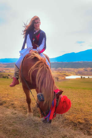 Bachevo, Bulgaria - March 16, 2019: Horse Easter or the day of Todor, lady in traditional bulgarian clothing riding a horse in the mountains