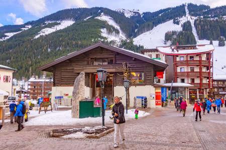 Saalbach, Austria - March 1, 2020: Town village street view in downtown of austrian ski resort and ski slopes