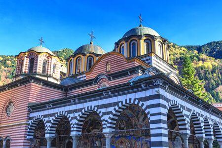 Bulgaria, Rila monastery church view and autumn mountain trees at background