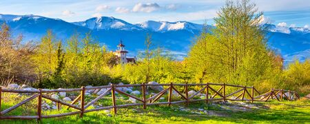 Bansko, Bulgaria spring landscape with the wooden fence, trees, tower of chalet and snowy Rila mountains peaks