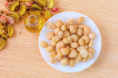 Bowl of macadamia nut oil and nuts, healthy food concept, top view