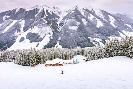 Austrian Alps, ski slope winter mountain landscape, snow forest and wooden house top view