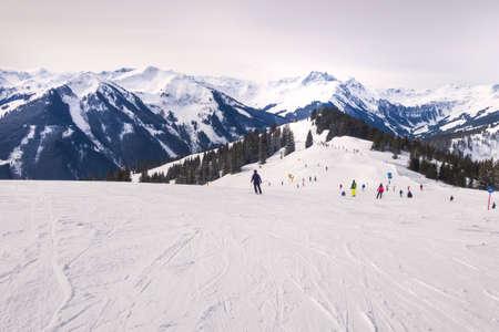 Saalbach, Austria, people skiing at ski slope of austrain winter resort and mountains panorama