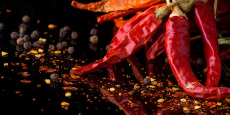 Red chilli pepper and flakes on  black