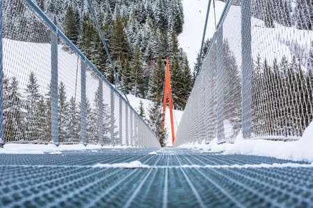 Golden Gate metal bridge near Saalbach, Austria, Europe, snow mountains and forest panorama