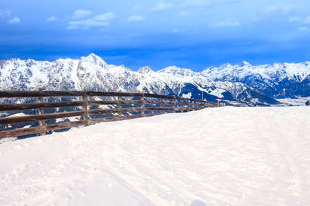 Panorama of snow mountain peaks landscape with wooden fence, Austria, Saalbach Фото со стока