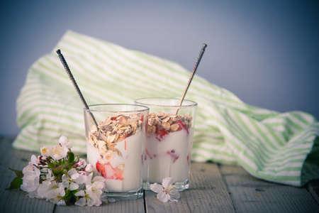 Healthy breakfast, muesli with fresh strawberry and yogurt two glasses and white flowers stylized photo