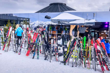 Saalbach, Austria - March 2, 2020: Many skis near restaurant on the slope, people Редакционное