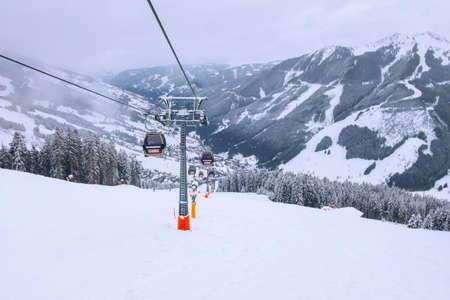 Saalbach, Austria - March 3, 2020: Bernkogelbahn cable car cabins, ski lift and ski slope in Saalbach Hinterglemm resort, Alps, Europe Редакционное