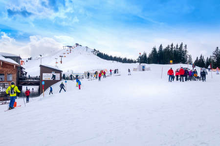 Saalbach, Austria - March 2, 2020: Skiers and snowboardes on the ski slope, wooden restaurant behind