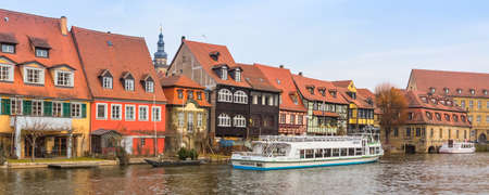 Bamberg, Germany - Ferbuary 19, 2017: Bamberg city center panorama with river, half-timbered colorful houses on water and boat Редакционное