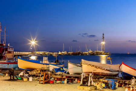 Pomorie, Bulgaria beachfront sea panorama with boats in the town and seaside resort on Black sea, blue hour dusk view