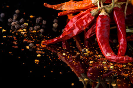 Red chilli pepper and flakes on a black background with reflection and copy space Stock fotó
