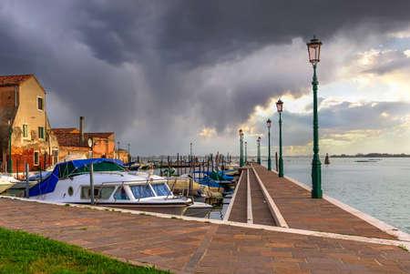 Cloudy view of Burano island harbor, marina, famous Venice landmark, Veneto region, Italy