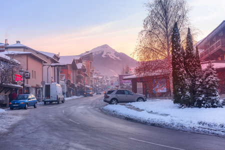 Bansko, Bulgaria - December 6, 2019: Pirin street view, traditional houses and Todorka snow mountain peak in bulgarian ski resort