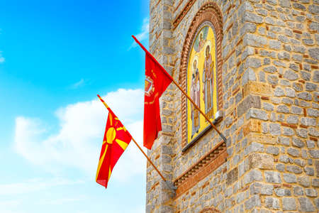 Ohrid, North Macedonia, close-up St. Clement Church at Plaosnik site with flags and mosaic icon on the bell tower Standard-Bild