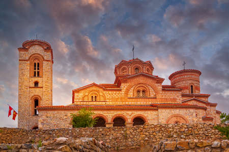 Ohrid, North Macedonia, St. Clement Church at Plaosnik site with flags and sunset sky