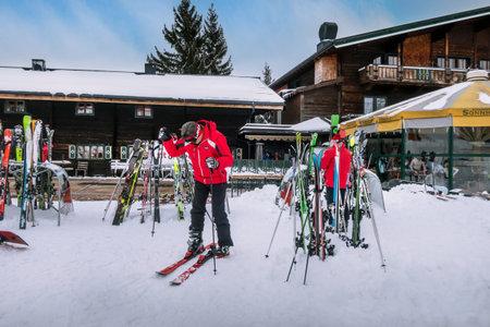 Saalbach, Austria - March 3, 2020: People preparing for skiing near ski slope restaurant