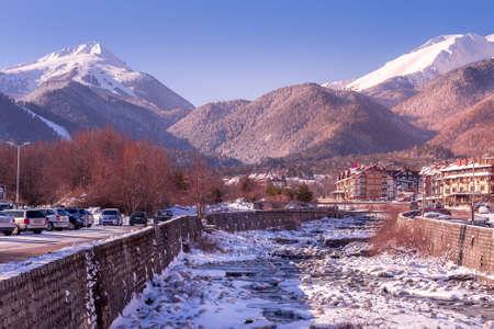 Bansko, Bulgaria - January 28, 2021: Glazne river in bulgarian town, hotel houses and snow Pirin mountains peaks