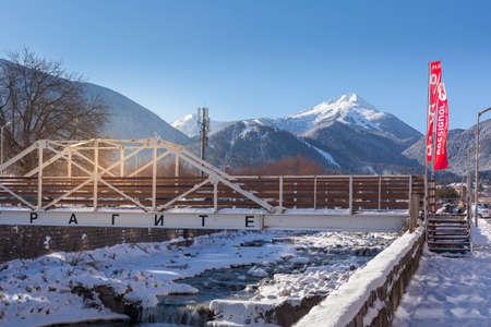 Bansko, Bulgaria - January 28, 2021: Glazne river in bulgarian town, bridge and snow Pirin mountains peaks 新闻类图片