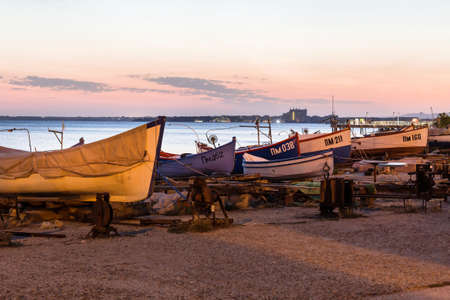 Pomorie, Bulgaria - September 15, 2020: Beachfront sea panorama with fishing boats in the town and seaside resort on Black sea, sunset view