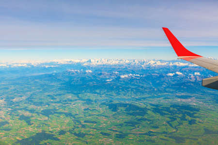 Aerial airplane view on the Swiss Alps with green valley and snow peaks, Switzerland above clouds 免版税图像
