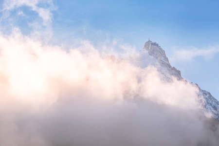 Aiguille du Midi peak between clouds, mountain in the Mont Blanc massif in the French Alps, Chamonix, France 免版税图像