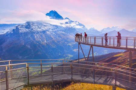 Grindelwald, Switzerland - October 10, 2019: People on sky cliff walk metal bridge at First peak of Swiss Alps mountain, snow peaks pink sunset panorama
