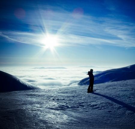 éxtasis: Esquí que viaja silueta de la mujer en el increíble paisaje de montaña invierno, sobre las nubes, frente a la puesta de sol cielo