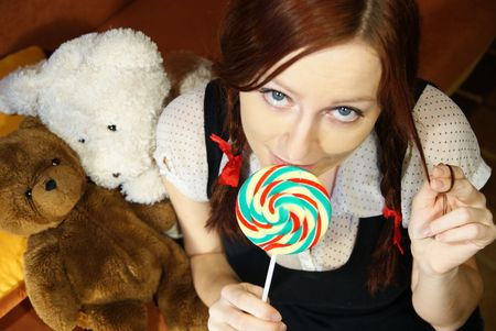 red head girl:   Red head girl with lollipop and teddy bears Stock Photo