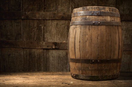 barrels: Still life: old wooden pin of beer, glass of beer and wheat on the table in the cellar.