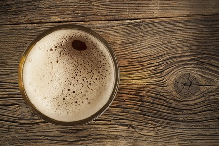 rusty background: Beer barrel with beer glass on table on wooden background