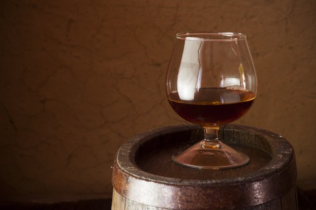 drunks: glass of brandy in the cellar with old barrels stacked in a row