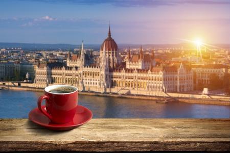 Koffie in kop op houten lijst tegenover een mening van de stad van Boedapest.