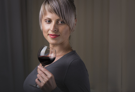 eyesclosed: Closeup portrait of young female customer drinking red wine with eyes closed